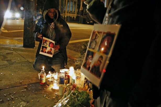 Daryis Mackey holds a photo montage of shooting victims Yalani Chinyamurindi, David Saucier, Harith Atchan and Manuel O�Neal after a vigil on Monday, January 12, 2015 at the scene of shooting at Laguna and Page in Hayes Valley in San Francisco, Calif..