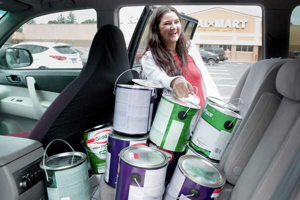 Nineteen-year-old Gabby Photos, of Bridgeport, fills her car with 50 cans of paint after shopping with her father Friday, July 29, 2016 at Walmart in Derby. The store is closing and paint was one of the best deals at $1 per can.