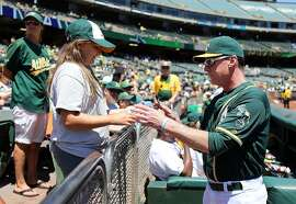 OAKLAND, CA - JULY 24:  Manager Bob Melvin #6 of the Oakland Athletics sings an autograph for a fan before the game against the Tampa Bay Rays at the Oakland-Alameda Coliseum on July 24, 2016 in Oakland, California.  (Photo by Don Feria/Getty Images)