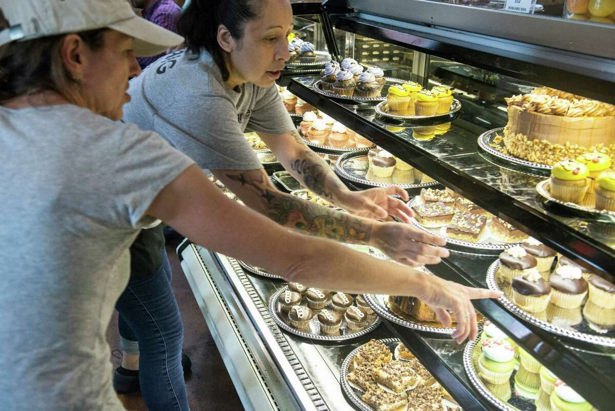 At Green Vegetarian Restaurant in The Pearl, waitress Ericka Rodulfo, center, helps Cindy Greenwood pick out a dozen vegan deserts for her friend's birthday.