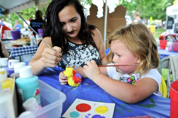 Eva Sasso, 4, of Newtown, paints a ceramic duck with the help of her mother Nicole at the Village Fair Days on the green in New Milford. Friday, July 29, 2016, in New Milford, Conn.