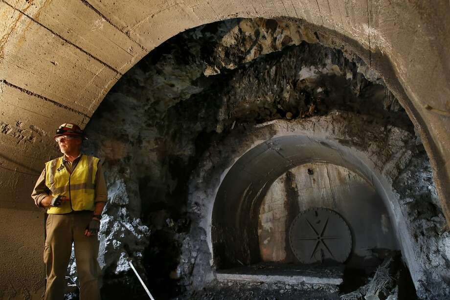 Project construction manager Robert Mues inside adit 8/9 one of several access tunnels that lead to Mountain Tunnel (bulkhead at right) near Groveland, California, on Thurs. July 28, 2016.  Mountain Tunnel, a key piece of the Hetch Hetchy water system is at risk of collapse, so this summer, the San Francisco Public Utilities Commission is preparing to repair the 19-mile-long tunnel just outside of Yosemite in a steep, hard-to-access wilderness area. Photo: Michael Macor, The Chronicle