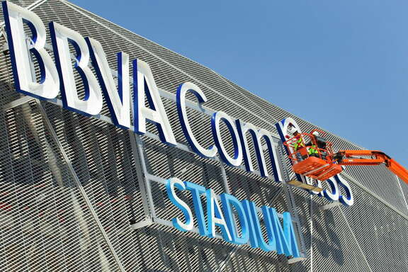 Luis Sanchez and Dagoberto Cruz, with IntexUnited, install the new sign at BBVA Compass Stadium Tuesday, April 24, 2012, in Houston. Finishing touches are being put on the new home of the Houston Dynamo. The stadium is scheduled to host its first Major League Soccer game May 12 against D.C. United. ( Brett Coomer / Houston Chronicle )