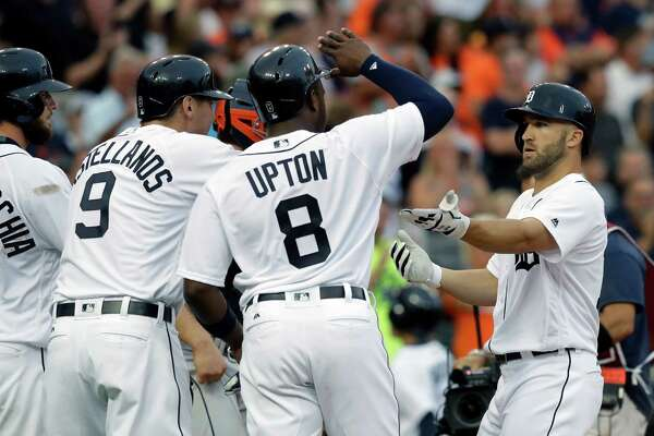 Detroit Tigers' Tyler Collins, right, is greeted at home plate by Jarrod Saltalamacchia, left, Nick Castellanos (9) and Justin Upton (8), after his three-run home run during the second inning of a baseball game against the Houston Astros, Friday, July 29, 2016, in Detroit. (AP Photo/Carlos Osorio)