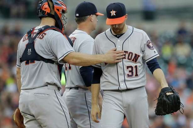 Houston Astros catcher Evan Gattis pats starting pitcher Collin McHugh on the chest after being pulled during the second inning of a baseball game against the Detroit Tigers, Friday, July 29, 2016, in Detroit. (AP Photo/Carlos Osorio)