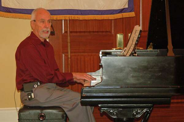 George Ubogy, a local doctor who is also a classically trained musician, spoke before the Greenwich Retired Men's Association in Greenwich Wednesday. He played the piano as he delivered a lecture on the importance of music.