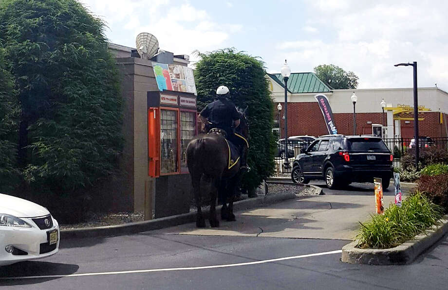 Saratoga Springs Realtor Kasandra Carda captured Springs Officer John Sesselman ordering a cup of coffee for himself and a glazed munchkin for his horse partner, King Tut, at a Dunkin' Donuts drive-thru in Saratoga Springs, N.Y.  (@Kasandrarealtor)