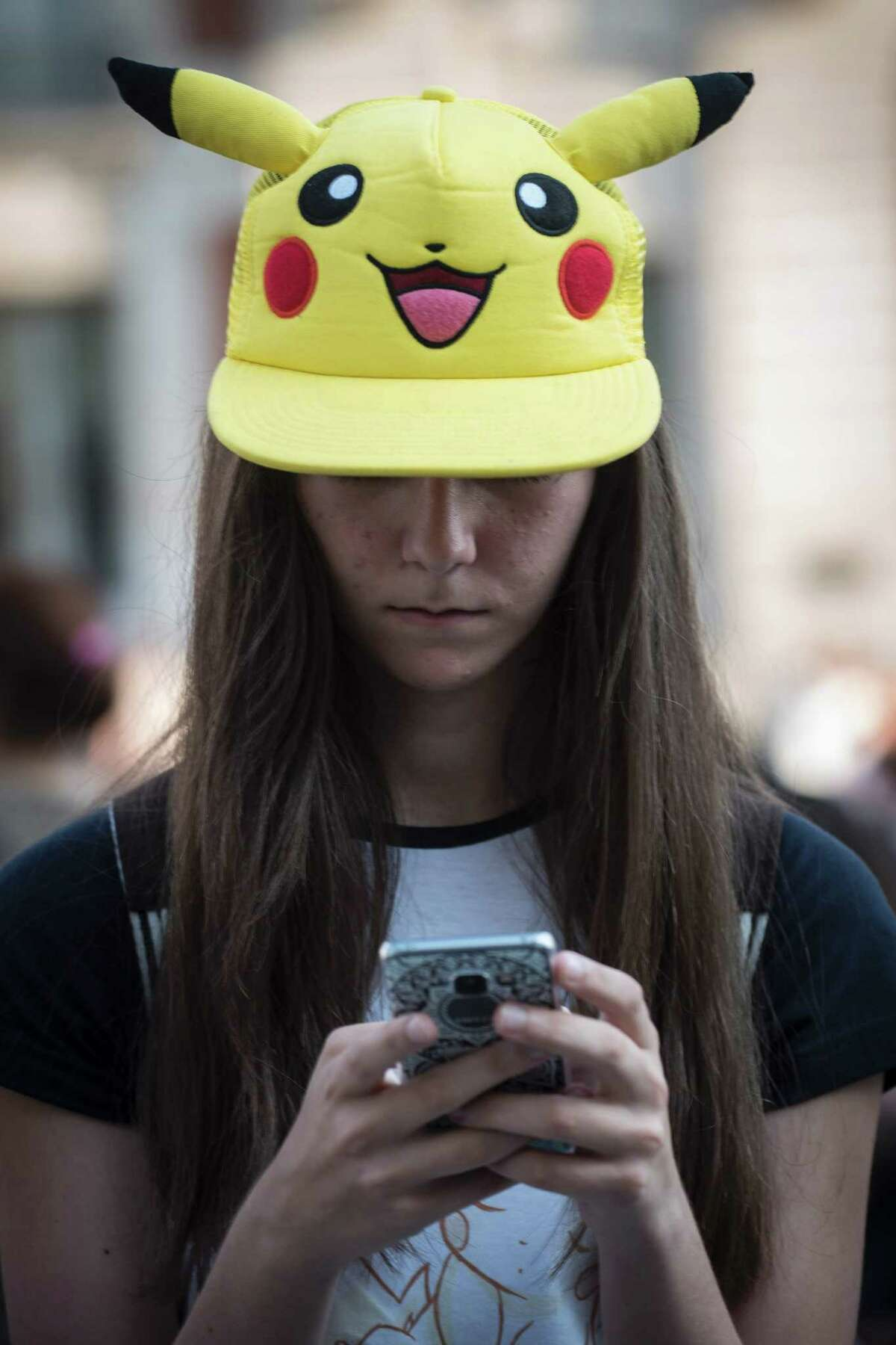 A girl sporting a Pikachu hat uses the