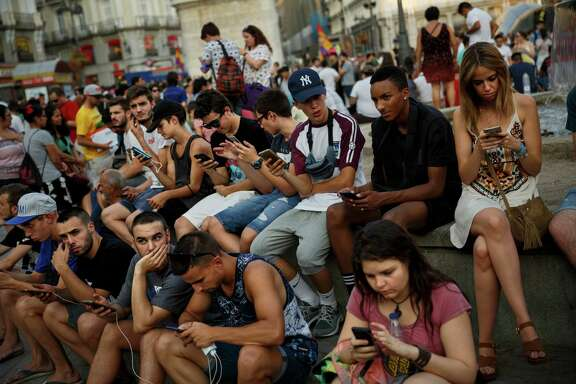 Spanish fans play the addictive Pokemon Go game during a gathering in central Madrid, Spain, Thursday, July 28, 2016, to play the computer game.  In the game players try to capture, battle, and train virtual creatures in their real world locations using the GPS and camera on their smart devices. (AP Photo/Daniel Ochoa de Olza)
