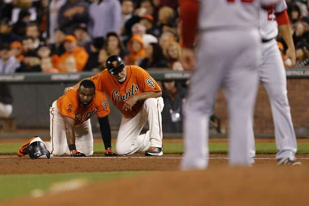Giants' first base coach Bill Hayes checks on Denard Span after Span tripped over the base beating out the throw for a single in the 8th inning, as the San Francisco Giants take on the Washington Nationals at AT&T Park in San Francisco, California, on Fri. July 29, 2016.