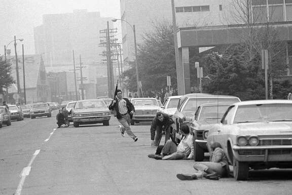 In this Jan. 7, 1973, file photo, a plainclothes police officer runs for cover as he moves into the area of the burning Howard Johnson Hotel in New Orleans. Mark James Essex, a member of the Black Panthers who was discharged from the Navy for going AWOL, killed nine people in New Orleans, including five police officers, in two sniper attacks. Essex is shot more than 200 times by police sharpshooters.