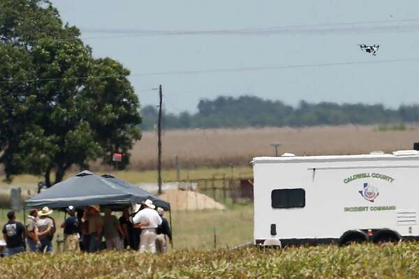 A drone is seen flying as first responders and investigators appear at a scene of a balloon crash that reports indicate took the lives of 16 people near Maxwell, Texas in Caldwell County on Saturday, July 30, 2016.