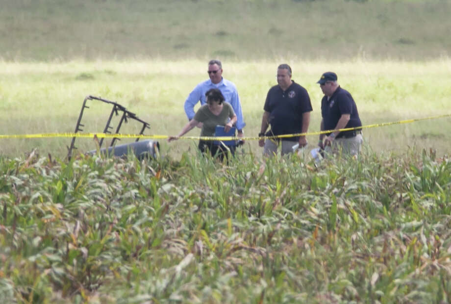 """The partial frame of a hot air balloon is visible above a crop field as investigators comb the wreckage of a crash Saturday morning, July 30, 2016, near XXX, Texas. Authorities say the accident caused a """"significant loss of life."""" (Ralph Barrera/Austin American-Statesman via AP) Photo: Ralph Barrera, AP / Austin American-Statesman"""