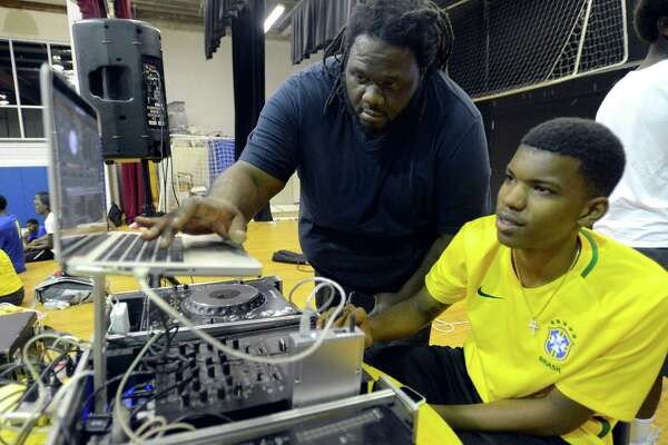 Marco Bender, A.K.A. Big MX, helps Voshon Natteal of Stamford set up a laptop that Natteal uses to mix jams he plays during a summer league basketball program at the Yerwood Center in Stamford.
