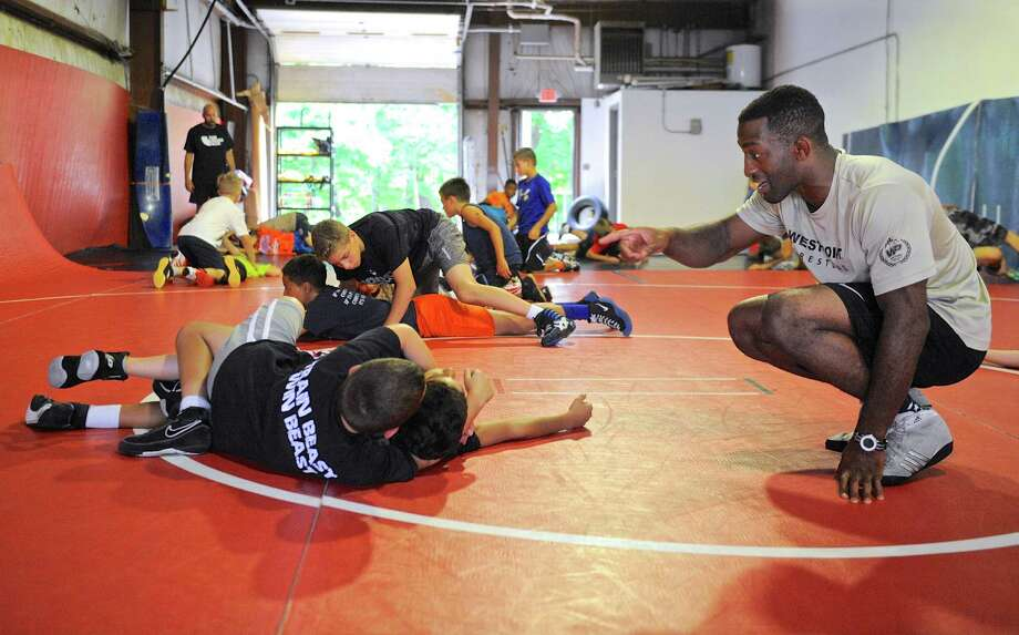 Army West Point assistant wrestling coach Chris Chionuma works with Elias Sturdedant, 12, and Dylan Mastroianni, 9, at the Beast Training Wrestling Club, in Danbury, on Saturday. July 30, 2016, in Danbury, Conn. It was part of a 3 day camp at the club. Photo: H John Voorhees III / Hearst Connecticut Media / The News-Times