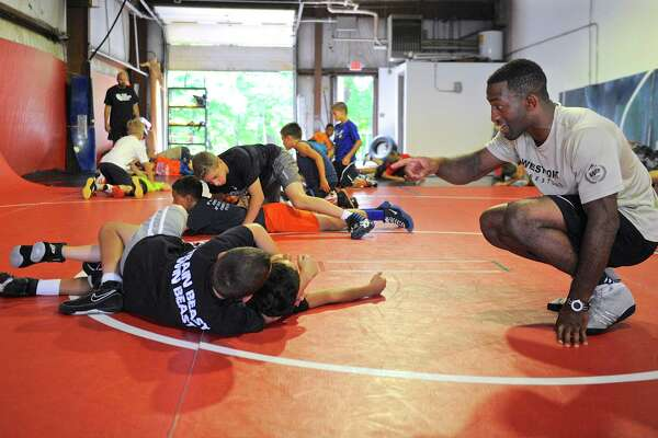 Army West Point assistant wrestling coach Chris Chionuma works with Elias Sturdedant, 12, and Dylan Mastroianni, 9, at the Beast Training Wrestling Club, in Danbury, on Saturday. July 30, 2016, in Danbury, Conn. It was part of a 3 day camp at the club.