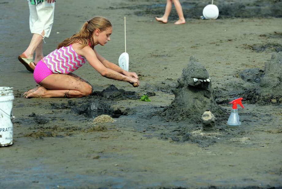 Sierra Wood, 12, of Stamford, works hard to complete a sea monster sand sculpture with help from her friend Eva Kenny, 12, (not pictured) during the Milford Arts Council Annual Sand Sculpture Competition held at Walnut Beach in Milford, Conn., on Saturday  July 30, 2016. This annual event draws over 50 sand sculptors and hundreds of spectators each year. Photo: Christian Abraham, Hearst Connecticut Media / Connecticut Post