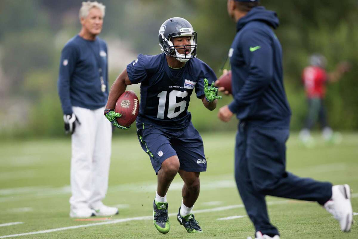 Seahawks wide receiver Tyler Lockett runs a drill as head coach Pete Carroll watches during the first day of training camp, at Virginia Mason Athletic Center in Renton on Saturday, July 30, 2016.