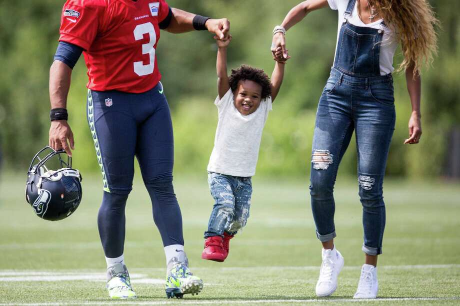 Seahawks quarterback Russell Wilson and his wife Ciara lift her son Future Zahir Wilburn as they walk off the field following the first day of training camp, at Virginia Mason Athletic Center in Renton on Saturday, July 30, 2016. Photo: GRANT HINDSLEY, SEATTLEPI.COM / SEATTLEPI.COM