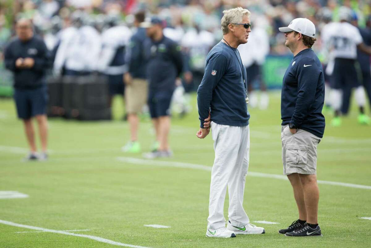 Seahawks head coach Pete Carroll talks with general manager John Schneider during the first day of training camp, at Virginia Mason Athletic Center in Renton on Saturday, July 30, 2016.