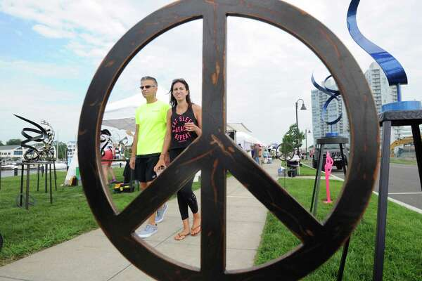 Framed through the steel sculpture peace symbol work of artist Joe Sorge, Stacey Callahan of Stamford and her father, Richard Nathan, left, enjoy the art at the Stamford Arts Festival at Harbor Point waterfront in Stamford, Conn., Saturday, July 30, 2016. The show has over 100 participating artists, has Sunday hours of 10 a.m. to 5 p.m., and is located at Stamford's Harbor Point Road/Atlantic Street.