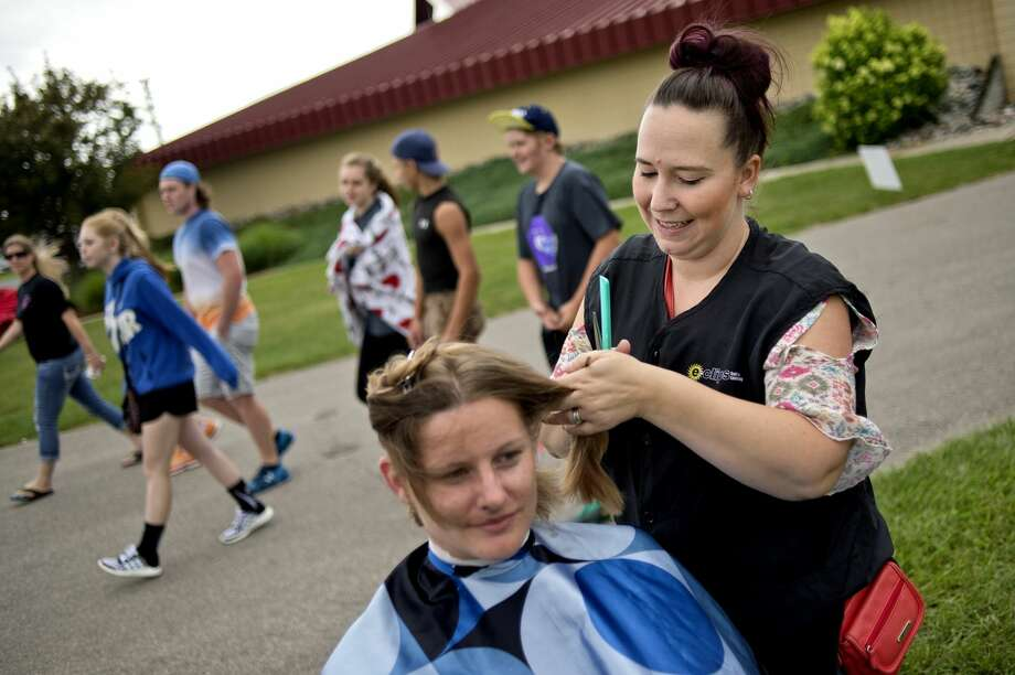E-Clips Hair & Tanning stylist Jennifer McPeek, right, cuts Amanda Ballard's hair for a donation during Relay For Life of Midland County on Saturday at the Midland County Fairgrounds. Ballard said that she has had family and friends affected by cancer and thought it was a good idea to donate the hair for wigs for cancer patients. Photo: NICK KING   Nking@mdn.net