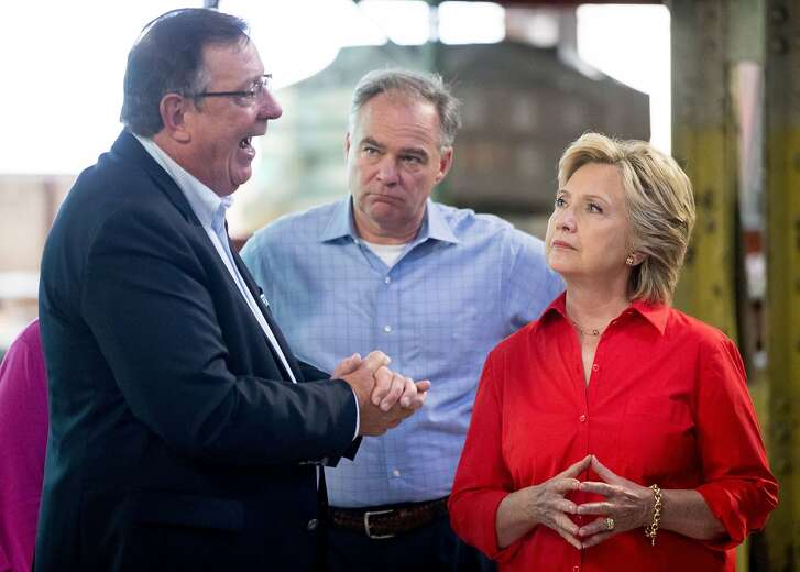 Johnstown Wire Technologies CEO Ron Shaffer, left, speaks with Democratic presidential candidate Hillary Clinton, right, accompanied by Democratic Vice Presidential candidate, Sen. Tim Kaine, D-Va., center, as they tour a Johnstown Wire Technologies factory in Johnstown, Pa., Saturday, July 30, 2016. Clinton and Kaine are on a three day bus tour through the rust belt. (AP Photo/Andrew Harnik)