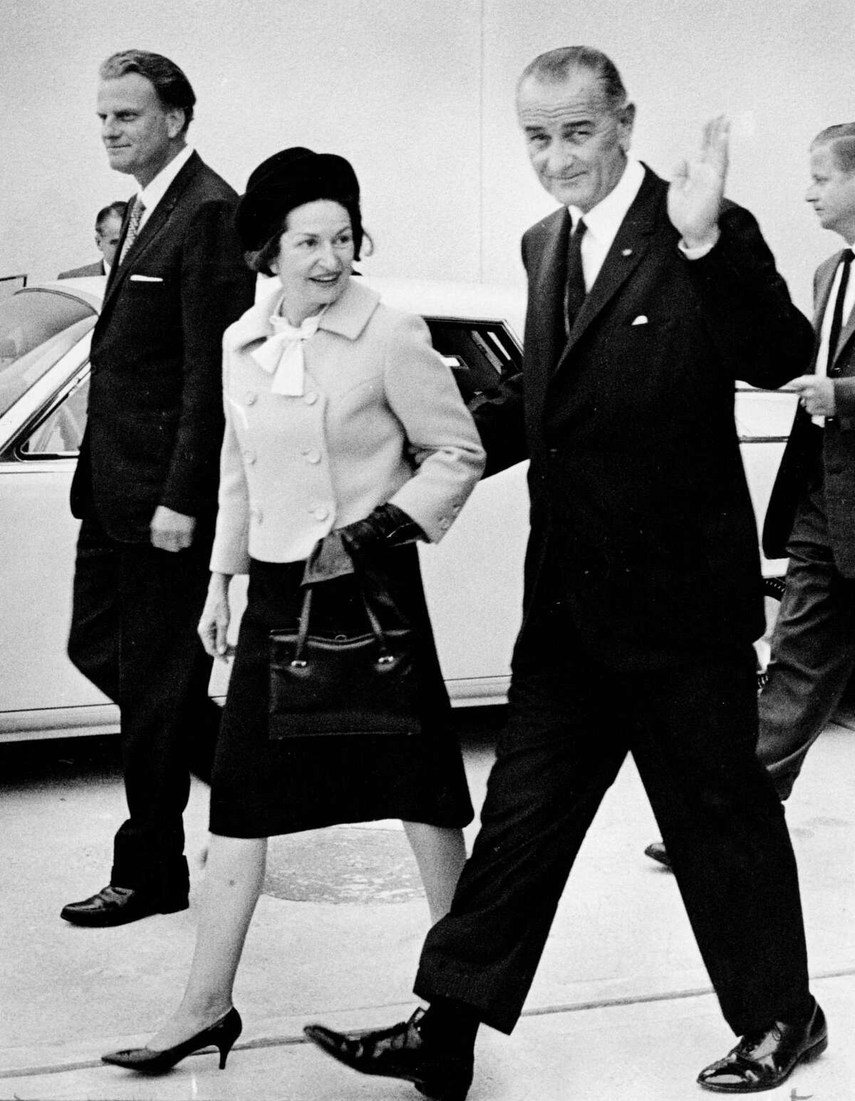 Lady Bird Johnson walks with President Lyndon Johnson and Rev. Billy Graham after an event in Houston on Nov. 25, 1965.