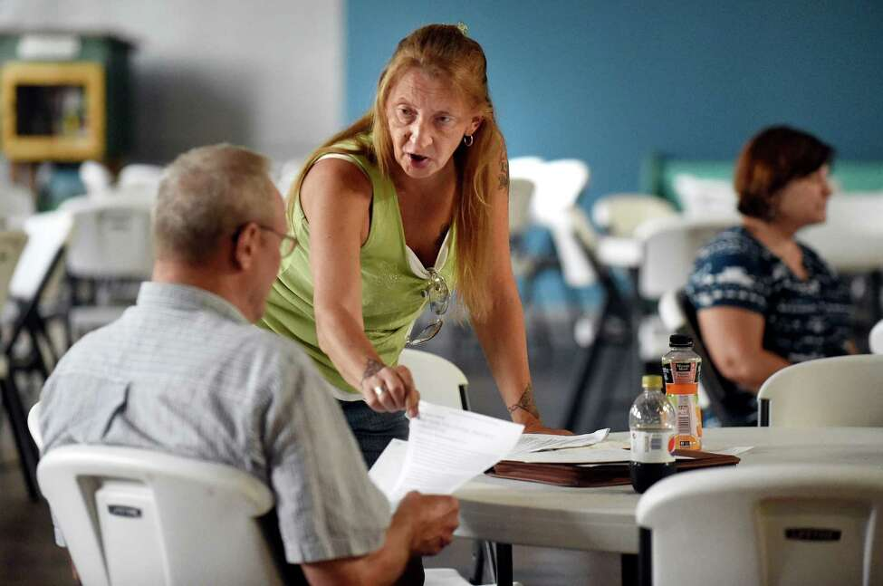 Village resident Loreen Hackett, center, talks with another resident on Saturday, July 30, 2016, at HAYC3 Armory in Hoosick Falls, N.Y. Only one doctor from Mount Sinai Hospital was present to discuss residents' blood test results, which created a long wait time. (Cindy Schultz / Times Union)