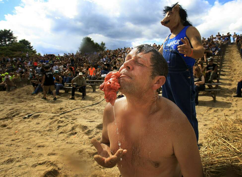 Gordon Hall of Old Orchard Beach emerges with a pigs foot in his mouth during the bobbing for pigs feet event at the Redneck Olympics in Hebron, Maine Saturday, August 3, 2013. (Photo by Gabe Souza/Portland Press Herald via Getty Images)