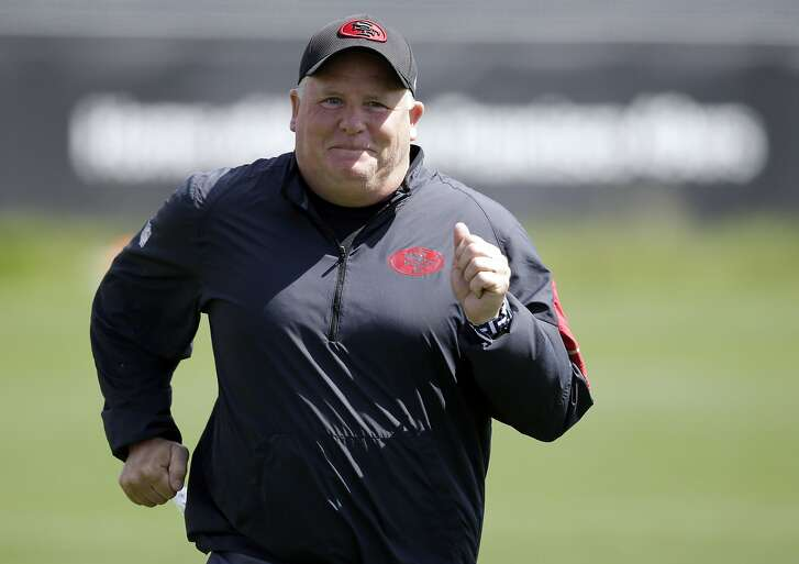 FILE - In this June 9, 2016, file photo, San Francisco 49ers head coach Chip Kelly runs during an NFL football practice in Santa Clara, Calif. Chip Kelly's first training camp in charge as new 49ers coach will likely be defined by an intense quarterback competition _ not to mention fierce fights for spots at several other key positions, such as wide receiver, cornerback and on the defensive line.  (AP Photo/Marcio Jose Sanchez, File)
