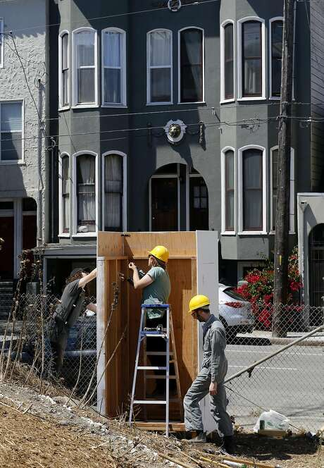 Designer Aaron Goldstein, (right) along with his partners Adam Miller, (left) and Alex Spatzier of AAA Services are  building a wooden column which will have an inflatable archway to mark an entrance into the Hayes Valley Art Works, an art activation site where the Fell St. offramp used to be near Octavia, in San Francisco, California, as seen on Sat. July 30, 2016. Photo: Michael Macor, The Chronicle