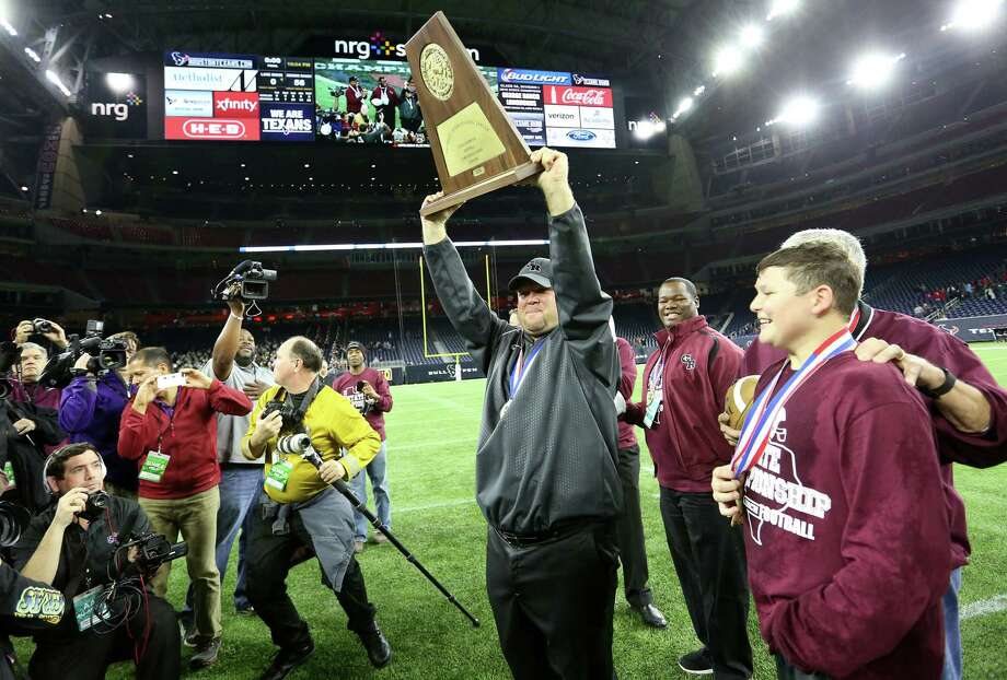 George Ranch head coach Ricky Tullos  holds up the championship trophy after the teams 56-0 win over Mansfield Lake Ridge for the 5A Div. 1 championship football game on  Friday, Dec. 18, 2015, in Houston.  ( Elizabeth Conley / Houston Chronicle ) Photo: Elizabeth Conley, Staff / © 2015 Houston Chronicle