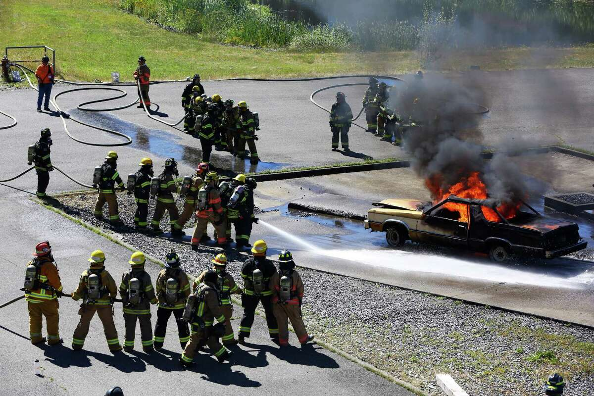 Campers in a hose line advance toward a burning car at Camp Blaze.