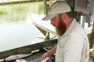 Jesse Griffiths, an Austin-based chef/restaurateur and enthusiastic outdoorsman, demonstrates the best methods of handling and cleaning fish as part of a multiday coastal fishing/cooking school.