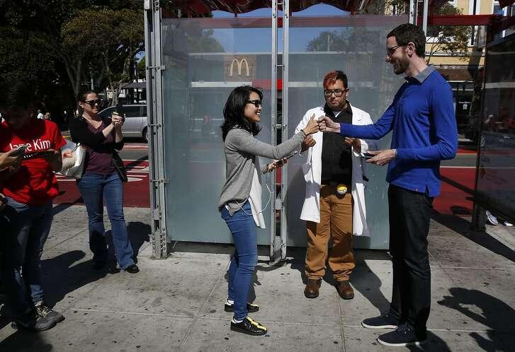 "State Senate candidates Jane Kim, left, and Scott Wiener bump fists as San Francisco Examiner reporter Joe Fitzgerald Rodriguez, center, kicks off their Pok�mon Go ""duel""  July 30, 2016 in San Francisco, Calif."