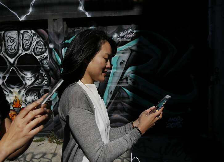 """State Senate candidate Jane Kim pauses in Lilac alley in the Mission while catching Pok�mon with volunteer and team member Noelle Duong, left, during a Pok�mon Go """"duel"""" between Kim and Scott Wiener July 30, 2016 in San Francisco, Calif."""
