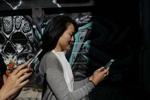 "State Senate candidate Jane Kim pauses in Lilac alley in the Mission while catching Pok�mon with volunteer and team member Noelle Duong, left, during a Pok�mon Go ""duel"" between Kim and Scott Wiener July 30, 2016 in San Francisco, Calif."