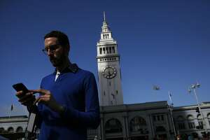 """State Senate candidate Scott Wiener attempts to catch Pok�mon outside of the Ferry Building  during a Pok�mon Go """"duel"""" between Jane Kim and Wiener July 30, 2016 in San Francisco, Calif."""
