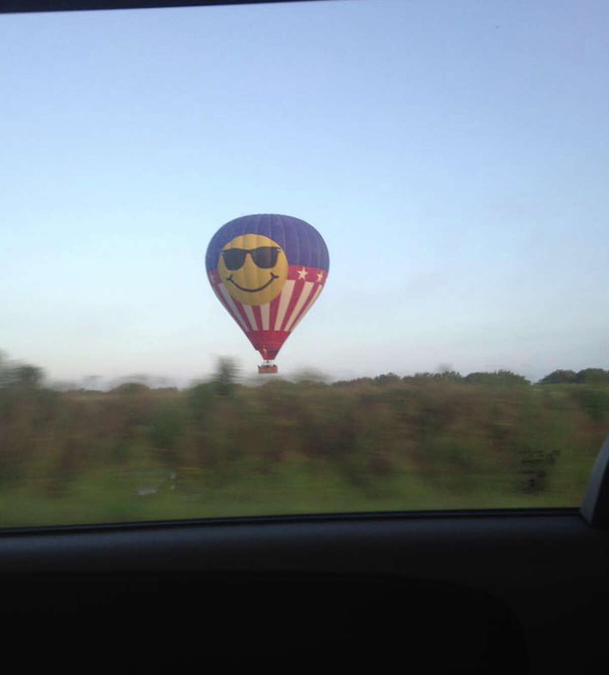 Investigators examine the scene of Saturday morning's crash of a large smiley face hot-air balloon, shown taking off below, near Lockhart. The NTSB says it is the deadliest such crash in U.S. history.