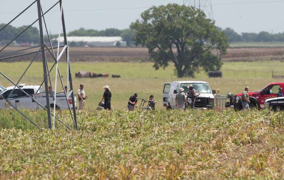 The partial frame of a hot-air balloon is visible above a crop field in Maxwell on Saturday as investigators comb the wreckage of an accident that killed at least 16 people near Lockhart. Photo: Ralph Barrera, MBR / Austin American-Statesman