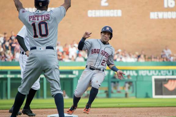 The Astros' Jose Altuve is held up at third base by Gary Pettis. Altuve had two hits and reached base three times, but a fielding mistake by the second baseman in the sixth inning allowed the Tigers' first run to score.