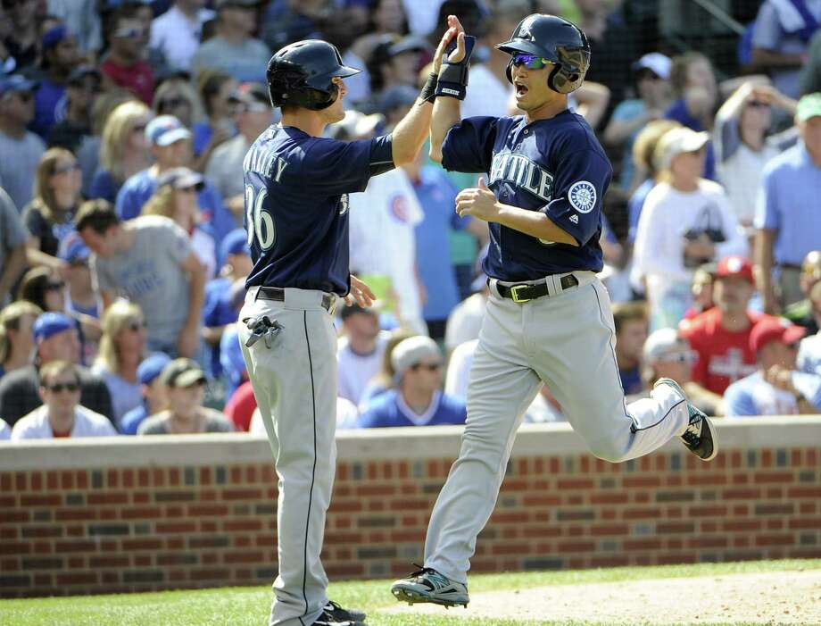 Seattle Mariners' Norichika Aoki, right, is greeted by Shawn O'Malley (36) after scoring against the Chicago Cubs during the eighth inning of an interleague baseball game, Saturday, July 30, 2016, in Chicago. (AP Photo/David Banks) ORG XMIT: CXC114 Photo: David Banks / FR165605 AP