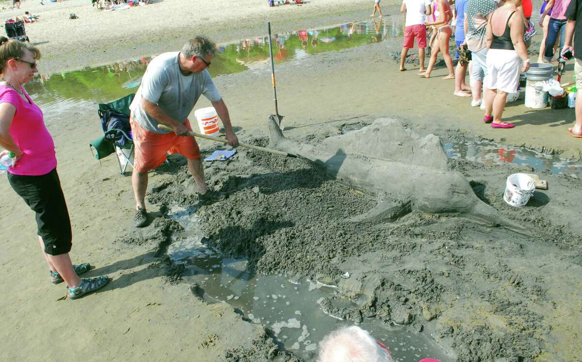 Beachgoers take part in the Milford Arts Council Annual Sand Sculpture Competition held at Walnut Beach in Milford on Saturday July 30. This event draws more than 50 sand sculptors and hundreds of spectators each year.
