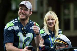 Seafair Torchlight Parade grand marshal Anna Faris and her husband Chris Pratt ride in a convertible in the annual parade through downtown Seattle on Saturday, July 30, 2016.