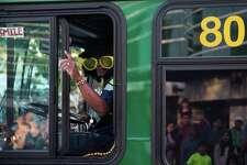 A King County Metro driver pilots a bus in an afro wig and sunglasses during the annual Seafair Torchlight Parade through downtown Seattle on Saturday, July 30, 2016.