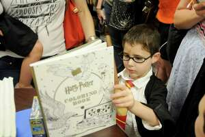 """Levi Kasner,6, look through a coloring book he won at the release party for the new Harry Potter book """"Harry Potter and the Cursed Child"""" at Blue Willow Bookshop Sunday July 31,2016.(Dave Rossman Photo)"""