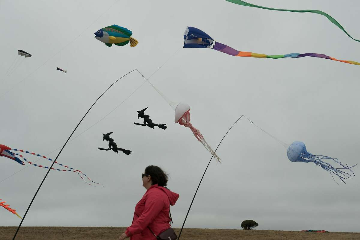 A woman walks through the annual Kite Festival in Berkeley, Calif. on Sunday, July 31, 2016. The festival attracted scores of people with intricate kites.