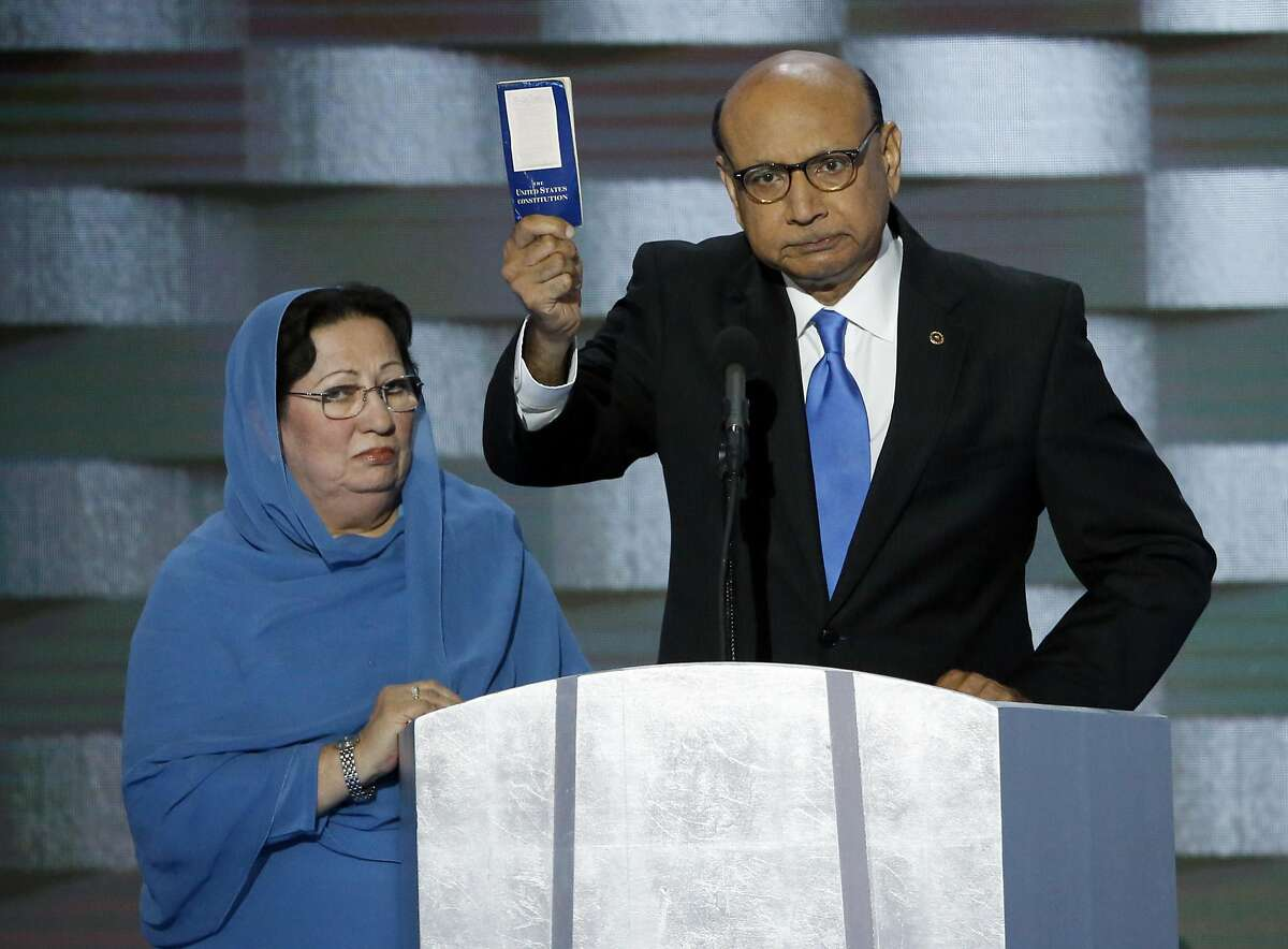 Khizr Khan holds a copy of Constitution of the United States, that he offered to lend to Donald Trump, with his wife Ghazala Khan, during the last day of the Democratic National Convention.