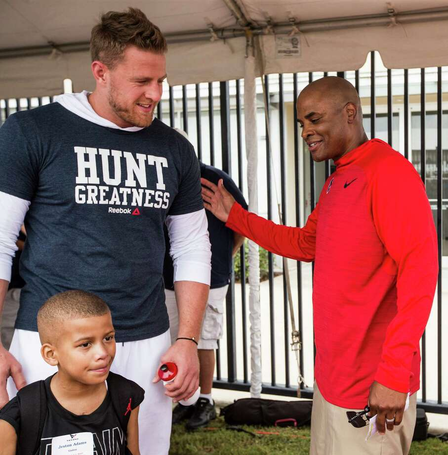 Houston Texans general manager Rick Smith greets defensive end J.J. Watt, left, and Texans fan Jeston Adams during Texans training camp at Houston Methodist Training Center on Sunday, July 31, 2016, in Houston. Photo: Brett Coomer, Houston Chronicle / © 2016 Houston Chronicle